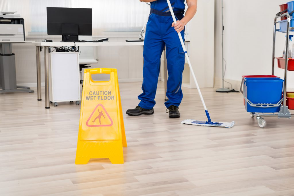 Low section of male janitor cleaning floor with mop in office